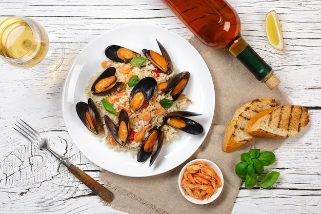 Fried rice with seafood mussels, shrimps and basil in a plate with wineglass, burlap and toasted baguette on white cracked wooden table. top view.