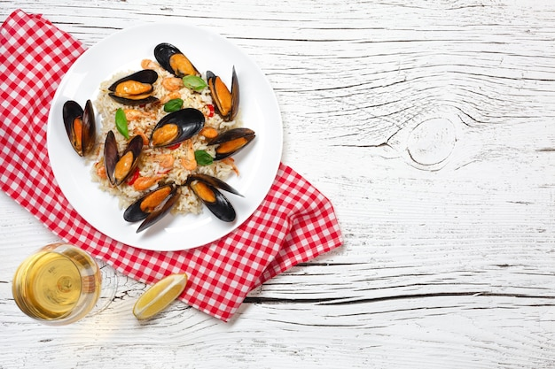 Fried rice with seafood mussels, shrimps and basil in a plate with wineglass, towel and toasted baguette on white cracked wooden table. top view.