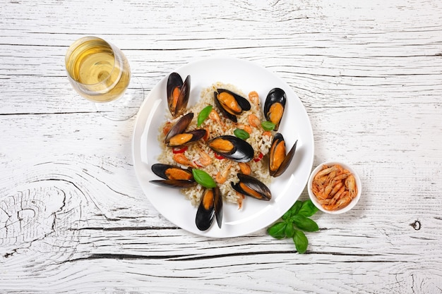 Fried rice with seafood mussels, shrimps and basil in a plate with wineglass on white cracked wooden table. top view.