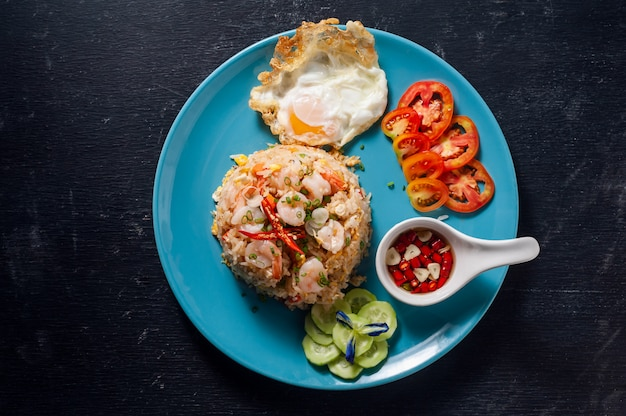 Fried rice with shrimp and fried egg on black wooden table, thai food.