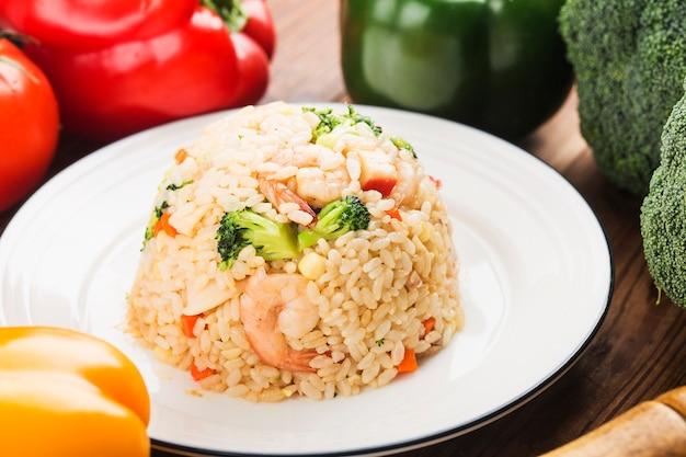 Жареный рис с креветками на белом блюде на деревянном столе с видом сверху