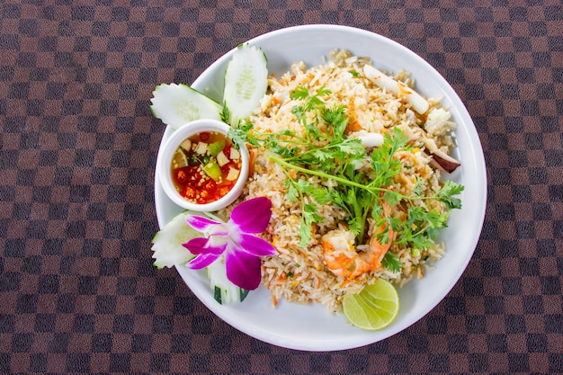 Fried rice with shrimp on the white ceramic dish decorated with orchid