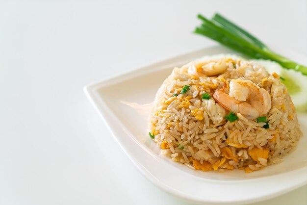 Жареный рис с креветками и крабами на белой тарелке