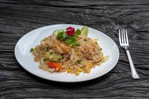 古い木製のテーブルの上の白い皿にエビと野菜のチャーハン、クローズアップ。タイ料理、タイ料理。レストランでのシーフードチャーハン