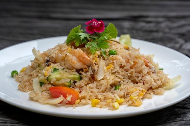 Жареный рис с креветками и овощами в белом блюде на старом деревянном столе, крупным планом. тайская кухня, тайская кухня. жареный рис с морепродуктами в ресторане