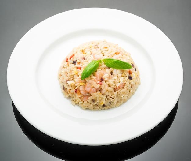 Жареный рис с креветками на тарелке, темный фон