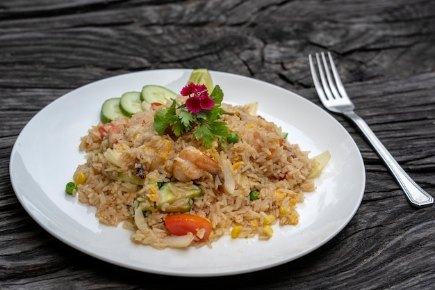 Fried rice with shrimps and vegetables in a white dish on an old wooden table, close up . thai food , thai cuisine. fried rice with seafood in the restaurant