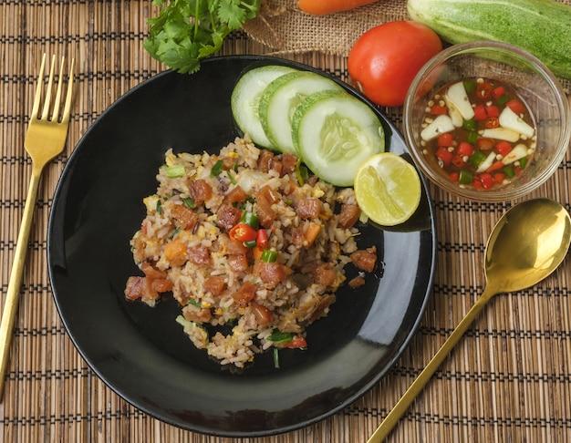 Жареный рис с нарезанной китайской колбасой украшают ингредиентами в деревянном стиле.