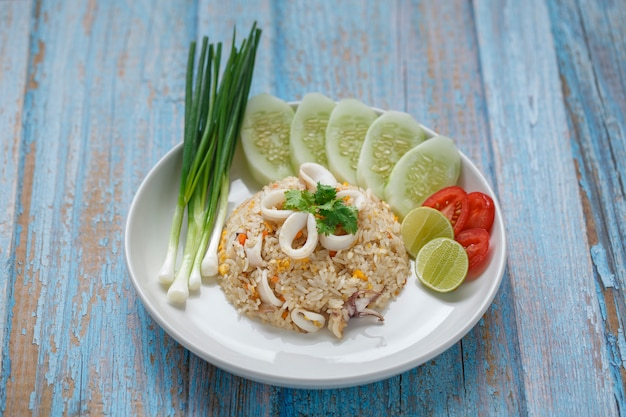Fried rice with squid served with spring onion, cucumber, coriander, tomato and lime