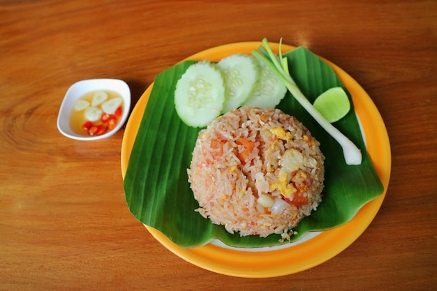 Fried rice with vagetable and banana leaf on orange plate thai style food concept