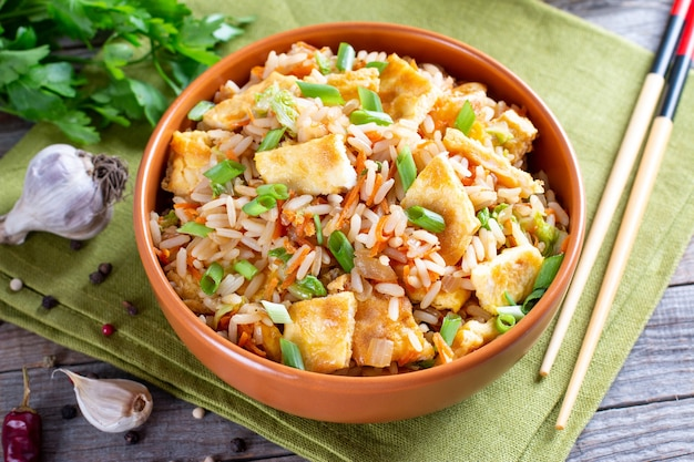 Fried rice with vegetables and fried eggs on a wooden table - chinese cuisine
