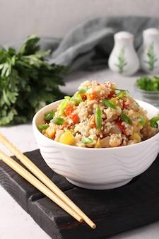Жареный рис с овощами, чесноком, имбирем и зеленым луком на сером столе. азиатская кухня. вегетарианская еда. вертикальный формат