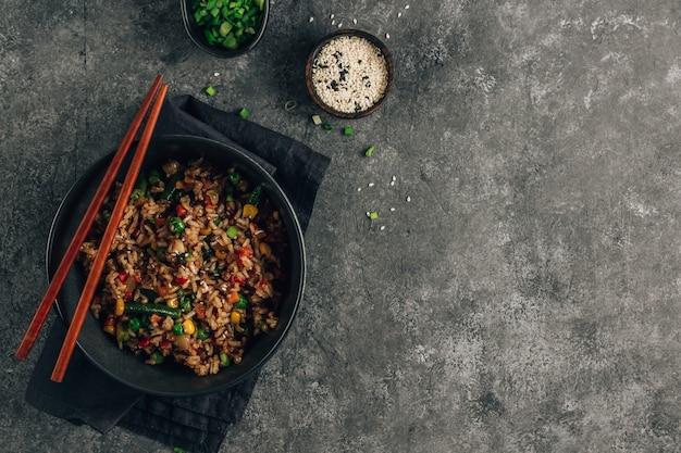 야채, 파, 참 깨와 돌 배경에 검은 그릇에 볶음밥.