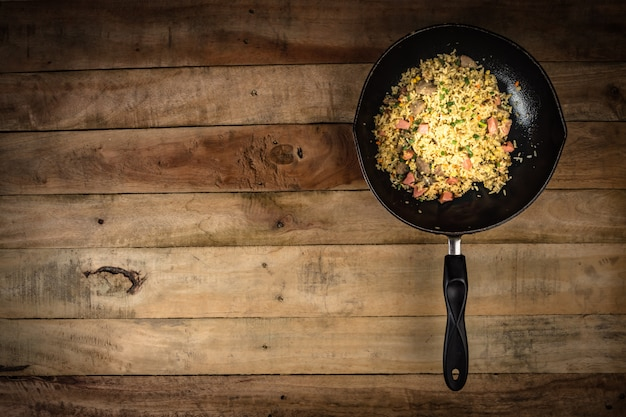Fried rice with vegetables, meat and fried eggs served on a plate with chopstick