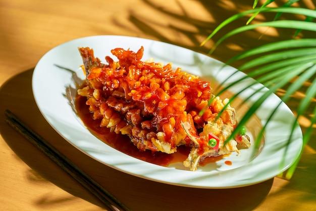 Жареная белочка из речного карпа или сонгшу ю в кисло-сладком соусе с кинзой, семенами кунжута и сычуаньским перцем в белой миске. китайская кухня