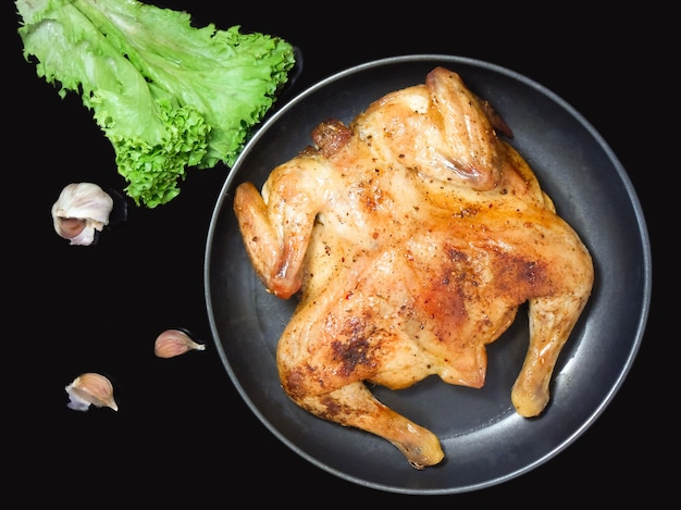 Fried roast chicken tabaka in frying pan on black background. garlic and salad. top view