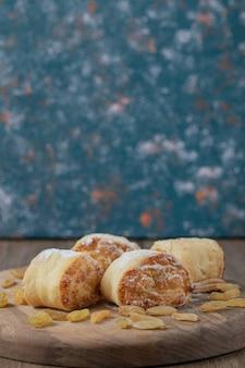 Жареные булочки с белым изюмом и сладкой начинкой на деревянной доске.