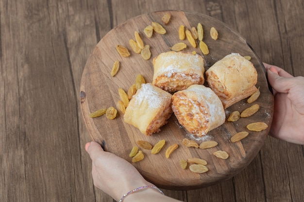 木の板に白いレーズンと甘い詰め物を添えた揚げロールクッキー。