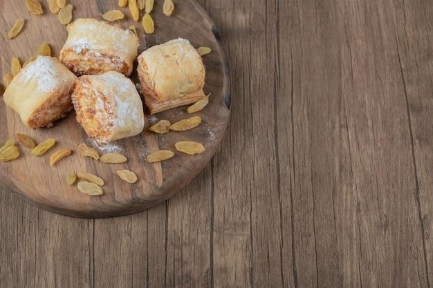 Biscotti fritti del rotolo con uvetta bianca e ripieni dolci su una tavola di legno.