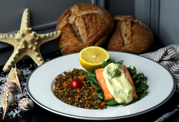 Fried salmon fillet garnished with sauce, served with roasted lentil and carrot