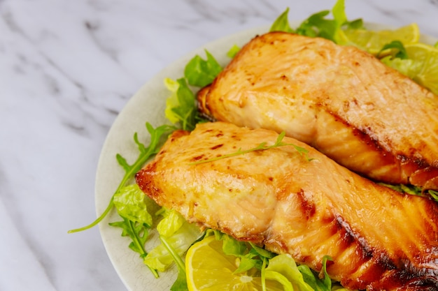 Fried salmon fillet with green salad on white plate. healthy food.