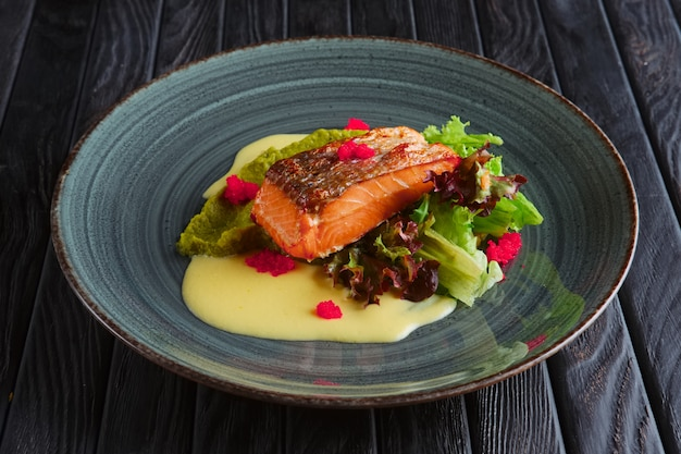 Fried salmon fillet with salad leaves and cream sauce decorated with caviar
