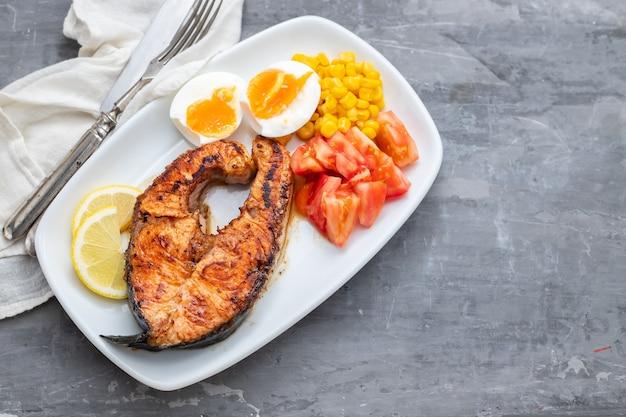 緑の背景に白い皿にゆで卵、トマト、トウモロコシと揚げ鮭