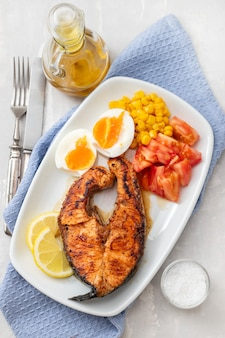 Fried salmon with boiled egg, tomato and corn on white dish
