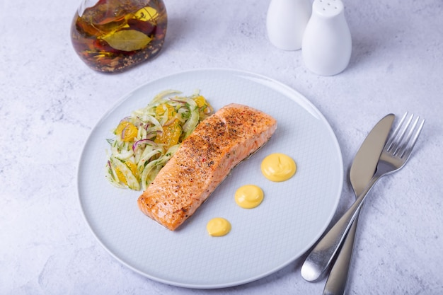 Fried salmon with fennel and orange salad with hollandaise sauce. french dish. close-up.