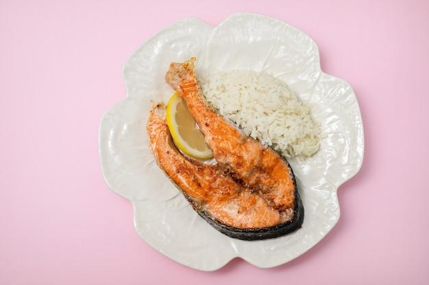 Жареный лосось с лимоном и отварным рисом на блюде