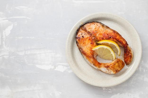 セラミック背景の皿にレモンと揚げサーモン