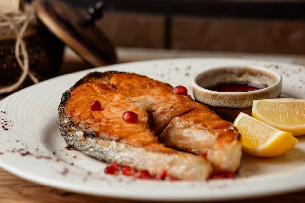Fried salmon with pomegranate seeds and lemon slices