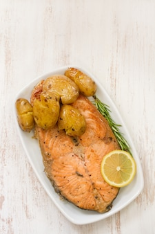 Fried salmon with potato on dish on white wooden surface