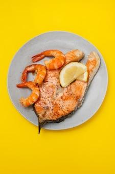 노란색 배경에 흰색 접시에 새우와 튀긴 연어