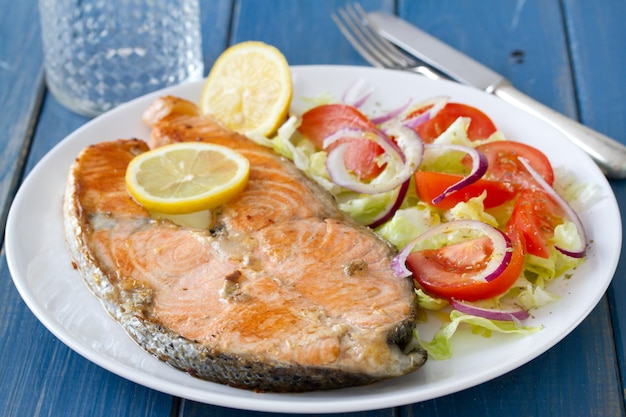 Fried salmon with vegetable salad and lemon on plate
