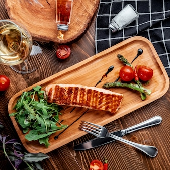 Fried salmon with vegetables on wooden board top view