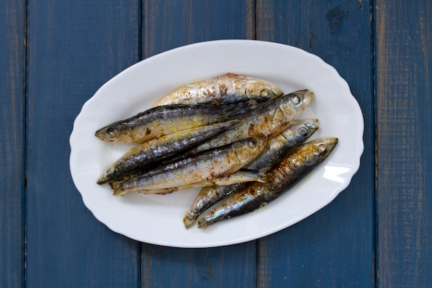 Fried sardines on white dish on blue wooden surface