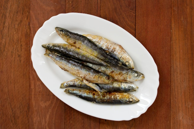 Fried sardines on white dish on brown wooden surface