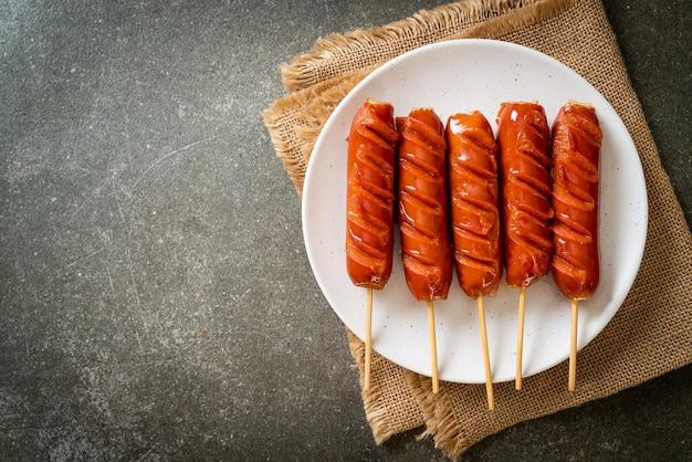 Шашлык из жареной колбасы на белой тарелке
