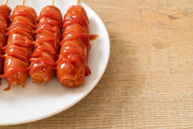 Шашлык из жареной колбасы с кетчупом на белой тарелке