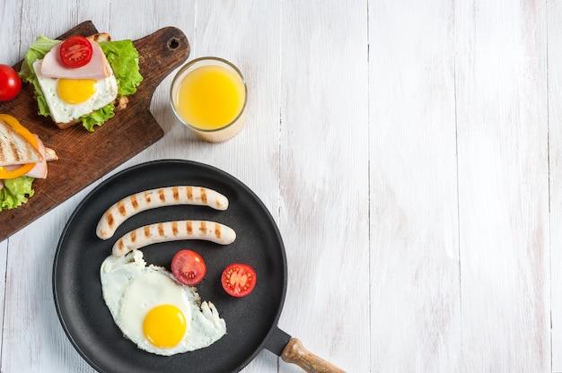 フライパンに卵と野菜を添えた揚げソーセージ。素朴な木の板にオレンジジュースとクロワッサンを添えた美味しい朝食。