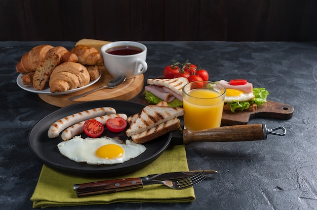 Fried sausage with eggs and vegetables on pan