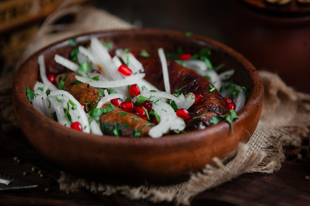 Fried sausage with onion and pomegranate
