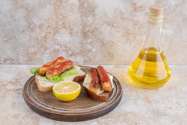 Жареные сосиски и сырные палочки на бутербродах с лимоном.