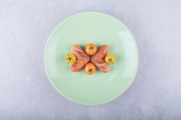튀긴 소시지와 녹색 접시에 체리 토마토입니다.