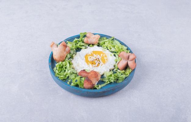 Жареные сосиски и яйцо на синей тарелке.