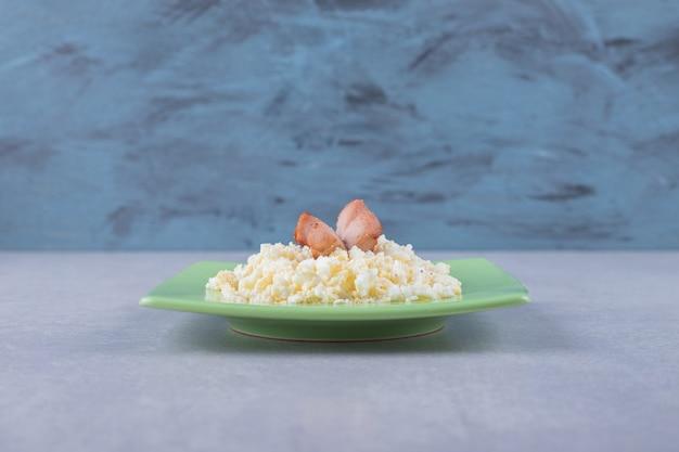 녹색 접시에 튀긴 소시지와 마카로니.
