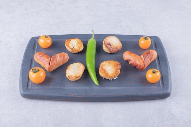 Жареные сосиски и картофель на темной доске.