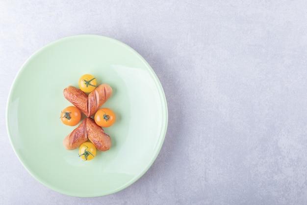 Salsicce fritte e pomodorini sul piatto verde.