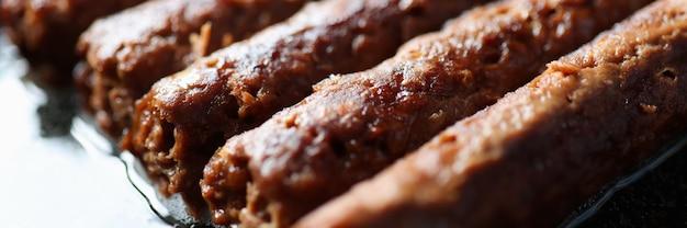 Жареные сосиски, лежащие в сковороде крупным планом